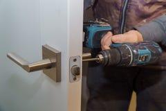 Εγκαταστήστε τη λαβή πορτών με μια κλειδαριά, ο ξυλουργός σφίγγει τη βίδα, χρησιμοποιώντας ένα ηλεκτρικό κατσαβίδι τρυπανιών στοκ εικόνες