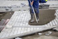 Εγκαταστήστε paver το πεζοδρόμιο με τις πέτρες επίστρωσης στοκ εικόνες