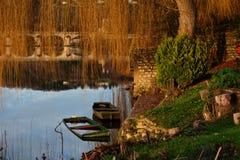Εγκαταλειμμένες βυθισμένες ξύλινες βάρκες στον ποταμό στο χαμηλό φως Στοκ εικόνα με δικαίωμα ελεύθερης χρήσης