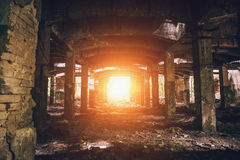 Εγκαταλειμμένη αποθήκη εμπορευμάτων με τις στήλες, σκοτεινή προοπτική σηράγγων με το φωτεινό φως στο τέλος Στοκ Εικόνες