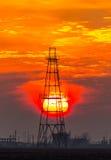 Εγκαταλειμμένη εγκατάσταση γεώτρησης πετρελαίου και φυσικού αερίου που σχεδιάζουν περίγραμμα στο δραματικό ουρανό βραδιού Στοκ Εικόνες