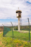 Εγκαταλειμμένος πύργος κιβωτίων σκοπών από ένα δίχτυ με οδοντωτό - καλώδιο Στοκ Φωτογραφία