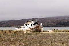 Εγκαταλειμμένο αλιευτικό σκάφος προσαραγμένο με το συννεφιάζω ουρανό στοκ εικόνα