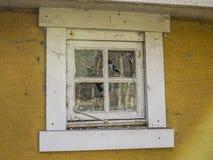 Εγκαταλειμμένο κίτρινο σπίτι με το σπασμένο παράθυρο Στοκ Εικόνες