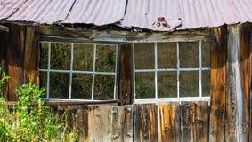 Εγκαταλειμμένο ξύλινο σπίτι με τη στέγη κασσίτερου στοκ φωτογραφίες