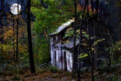 Εγκαταλειμμένο σπίτι στο δάσος στην ανατολή του φεγγαριού στοκ εικόνες