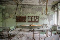 Εγκαταλειμμένο δωμάτιο κατηγορίας με τα έπιπλα και συντρίμμια σε Pripyat Στοκ Εικόνες