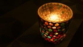Εγκαύματα κεριών σε ένα πολύχρωμο κηροπήγιο γυαλιού απόθεμα βίντεο