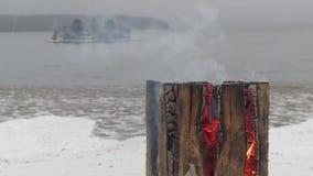 Εγκαύματα κούτσουρων στην ακτή μιας χειμερινής λίμνης απόθεμα βίντεο