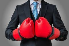 Εγκιβωτίζοντας επιχειρηματίας με τα κόκκινα γάντια στο γκρίζο υπόβαθρο Στοκ φωτογραφία με δικαίωμα ελεύθερης χρήσης