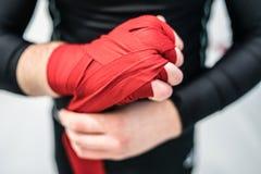 Εγκιβωτίζοντας μαχητής MMA που βάζει τα περικαλύμματα χεριών σε ετοιμότητα στοκ εικόνα