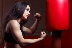 Εγκιβωτισμός γυναικών, που χτυπά ένα punching ομοίωμα Στοκ φωτογραφίες με δικαίωμα ελεύθερης χρήσης