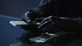 Εγκληματίας στα μαύρα γάντια που μετρούν τη δέσμη των χρημάτων που κερδίζεται για τη διάπραξη του εγκλήματος φιλμ μικρού μήκους