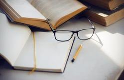 Εγκυκλοπαίδειες, ένα σημειωματάριο, γυαλιά, ένα κίτρινο μολύβι και ένα ανοικτό βιβλίο στοκ φωτογραφίες