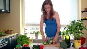 Εγκυμοσύνη και διατροφή Η έγκυος γυναίκα έκοψε τα λαχανικά πάπρικας στον πίνακα κουζινών απόθεμα βίντεο