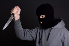 Εγκληματίας ατόμων στη μαύρη μάσκα με το μαχαίρι πέρα από το γκρι Στοκ Εικόνες