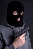 Εγκληματίας ατόμων στη μαύρη μάσκα με το πυροβόλο όπλο πέρα από το γκρι Στοκ εικόνες με δικαίωμα ελεύθερης χρήσης