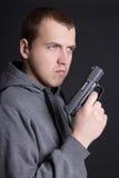 Εγκληματίας νεαρών άνδρων με το πυροβόλο όπλο πέρα από το γκρι Στοκ Εικόνες