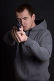Εγκληματίας νεαρών άνδρων που στοχεύει με το πυροβόλο όπλο πέρα από το γκρι Στοκ φωτογραφία με δικαίωμα ελεύθερης χρήσης