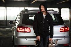 Εγκληματικό άτομο με το πυροβόλο όπλο και σχοινί που στέκεται κοντά στο αυτοκίνητο Στοκ Εικόνα