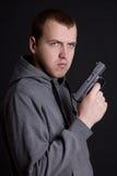 Εγκληματικό πυροβόλο όπλο εκμετάλλευσης νεαρών άνδρων πέρα από το γκρι Στοκ εικόνα με δικαίωμα ελεύθερης χρήσης