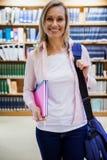 Εγχειρίδια εκμετάλλευσης γυναικών σπουδαστών στη βιβλιοθήκη στοκ εικόνα με δικαίωμα ελεύθερης χρήσης