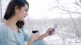 Εγχώρια άνεση, νέα γυναίκα με τη συσκευή στα χέρια που πίνουν τον καφέ και που κάθονται κοντά στο μεγάλο παράθυρο στο εσωτερικό φιλμ μικρού μήκους