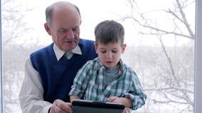 Εγχώρια εκπαίδευση, granddad και παιχνίδι εγγονών στην ταμπλέτα στο παιχνίδι Διαδικτύου στο δωμάτιο φιλμ μικρού μήκους