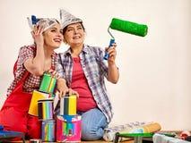Εγχώριες γυναίκες επισκευής που κρατούν την τράπεζα με το χρώμα για την ταπετσαρία Στοκ εικόνες με δικαίωμα ελεύθερης χρήσης