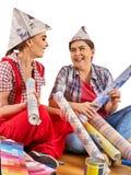 Εγχώριες γυναίκες επισκευής που κρατούν την τράπεζα με το χρώμα για την ταπετσαρία Στοκ Εικόνες