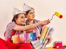 Εγχώριες γυναίκες επισκευής που κρατούν την τράπεζα με το χρώμα για την ταπετσαρία Στοκ Φωτογραφία