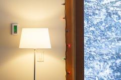 Εγχώριο εσωτερικό καθιστικό το χειμώνα με την ψηφιακή ηλεκτρονική θερμοστάτη, το λαμπτήρα πατωμάτων και την άποψη μέσω των παραθύ Στοκ Εικόνα
