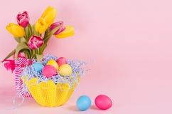 Εγχώριο ντεκόρ άνοιξη Πάσχας των κίτρινων τουλιπών, χρωματισμένα αυγά, δύο αυγά στο μαλακό ρόδινο υπόβαθρο κρητιδογραφιών στοκ φωτογραφία με δικαίωμα ελεύθερης χρήσης