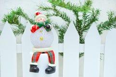 Εγχώριο ντεκόρ Χριστουγέννων Χιονάνθρωπος παιχνιδιών κοντά σε έναν άσπρο φράκτη με ένα δέντρο στοκ φωτογραφία με δικαίωμα ελεύθερης χρήσης