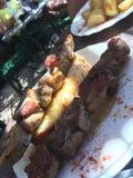 Εγχώριο BBQ που τρώνε steacks, πατάτες και ψημένο στη σχάρα ψωμί με το πετρέλαιο Στοκ Εικόνες