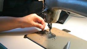 Εγχώριο seamstress που προετοιμάζει τη ράβοντας μηχανή για να εργαστεί Μοδίστρα που παίρνει έτοιμη φιλμ μικρού μήκους