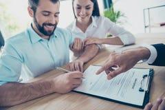 εδώ παρακαλώ υπογράψτε Το ευτυχές ζεύγος αγοράζει το καινούργιο σπίτι, ο δικηγόρος είναι δημόσιες σχέσεις στοκ φωτογραφίες