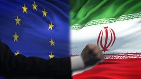 ΕΕ εναντίον της αντιμετώπισης του Ιράν, διαφωνία χωρών, πυγμές στο υπόβαθρο σημαιών φιλμ μικρού μήκους