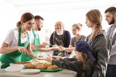 Εθελοντές που δίνουν τα τρόφιμα στους φτωχούς ανθρώπους στοκ εικόνες