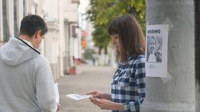 Εθελοντής κοριτσιών που διανέμει τα φυλλάδια για το ελλείπον παιδί απόθεμα βίντεο