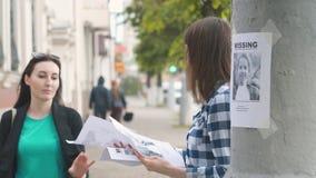 Εθελοντής κοριτσιών που διανέμει τα φυλλάδια για το ελλείπον παιδί, αργό MO απόθεμα βίντεο