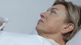 Εθελοντική ταΐζοντας ηλικιωμένη παραλυμένη γυναίκα που βρίσκεται στο νοσοκομειακό κρεβάτι, ανικανότητα απόθεμα βίντεο