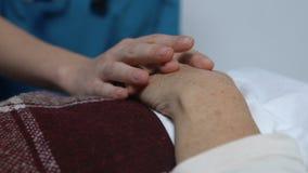 Εθελοντικό χέρι εκμετάλλευσης του ηλικίας θηλυκού ασθενή που βρίσκεται στο κρεβάτι, την προσοχή και την υποστήριξη απόθεμα βίντεο