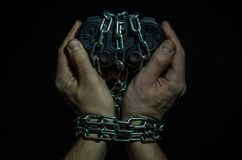 Εθισμένα χέρια του φορέα τυχερού παιχνιδιού με το πηδάλιο που αλυσοδένεται στις αλυσίδες που απομονώνονται στο μαύρο υπόβαθρο στοκ φωτογραφία