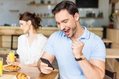 εθισμένος άνδρας που χρησιμοποιεί το smartphone και τη δυστυχισμένη συνεδρίαση γυναικών του Στοκ φωτογραφία με δικαίωμα ελεύθερης χρήσης
