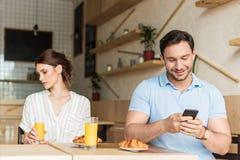 εθισμένος χαμογελώντας άνδρας που χρησιμοποιεί το smartphone και τη δυστυχισμένη συνεδρίαση γυναικών του Στοκ φωτογραφίες με δικαίωμα ελεύθερης χρήσης
