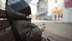Εθιστική συνεδρίαση smartphone μικρών παιδιών στον πάγκο στην οδό πόλεων Χαριτωμένο παιδί αγοράκι με το κινητό τηλέφωνο στον πάγκ φιλμ μικρού μήκους