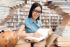 Εθνική ασιατική συνεδρίαση κοριτσιών στον πίνακα που περιβάλλεται από τα βιβλία στη βιβλιοθήκη Ο σπουδαστής γράφει στο σημειωματά στοκ εικόνες
