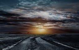 Εθνική οδός από το αμμοχάλικο στο ηλιοβασίλεμα στοκ εικόνες