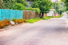 εθνική οδός με την άσφαλτο στην επαρχία Η χλόη και τα λουλούδια αυξάνονται στα περιθώρια κατά μήκος των ακρών Στοκ Εικόνες